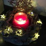 Kranz mit Sternen und einer Kerze